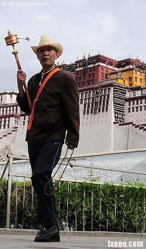 布达拉宫前手持转经筒的男人