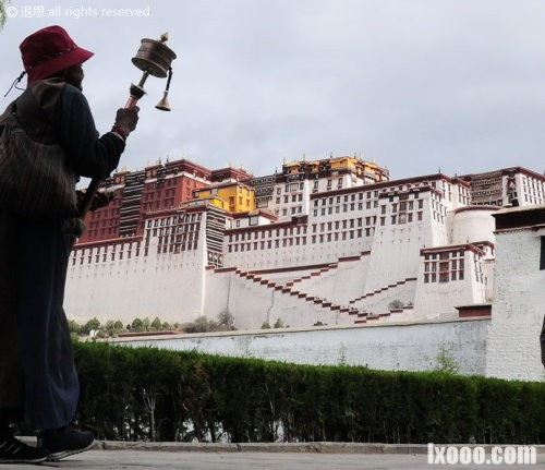 布达拉宫前手持转经筒的女人