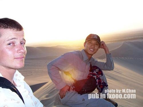 坐在敦煌鸣沙山上的摩凝(M.Chan)和刚刚认识的老外