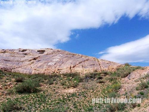 巴里坤怪石山上写着大漠悬棺的石壁
