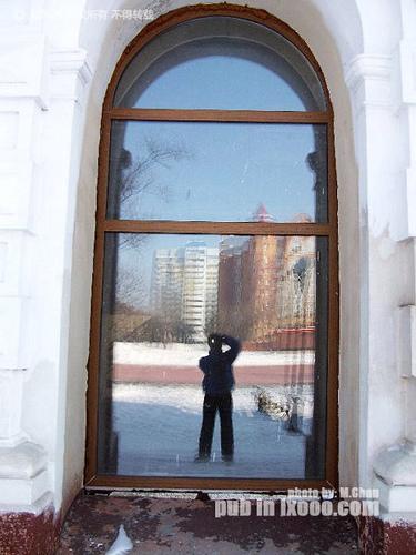 摩凝在布拉戈维申斯克胜利广场旁边建筑物窗户上的倒影